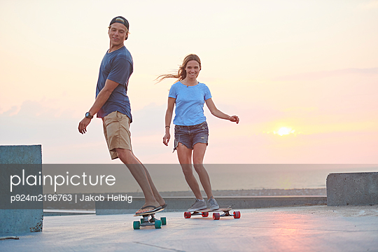 A young couple, man and woman skateboarding by the beach at sunset. - p924m2196763 by Jakob Helbig