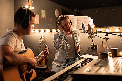 Men creating song in modern studio - p1166m2261749 by Cavan Images
