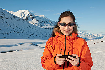 woman texting on her smartphone in the mountains of north Iceland - p1166m2269496 by Cavan Images
