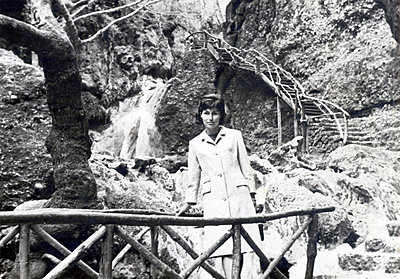 Young woman in front of small waterfall - p1541m2116870 by Ruth Botzenhardt