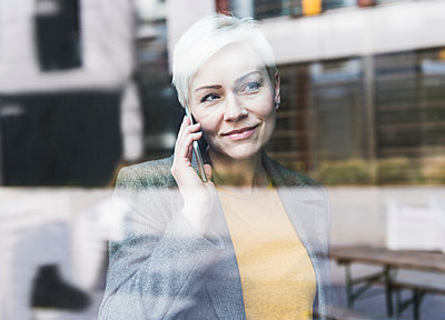 Portrait of confident businesswoman on cell phone behind windowpane - p300m1581454 by Uwe Umstätter