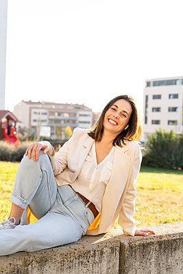 Smiling Businesswoman sitting in garden on sunny day - p300m2239949 by VITTA GALLERY