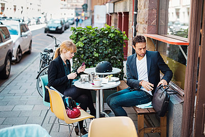 Business commuters sitting at sidewalk cafe - p426m1062550f by Maskot