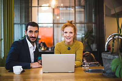Portrait of smiling female and male business colleagues sitting with laptop at table in office - p426m2089028 by Maskot