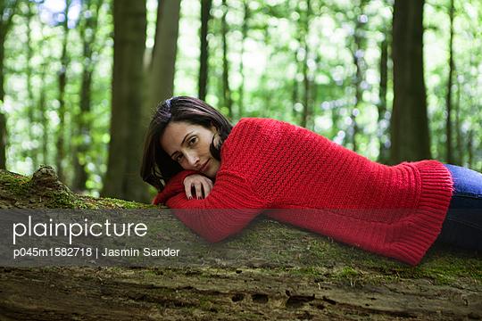 Frau liegt auf einem Baumstamm  - p045m1582718 von Jasmin Sander