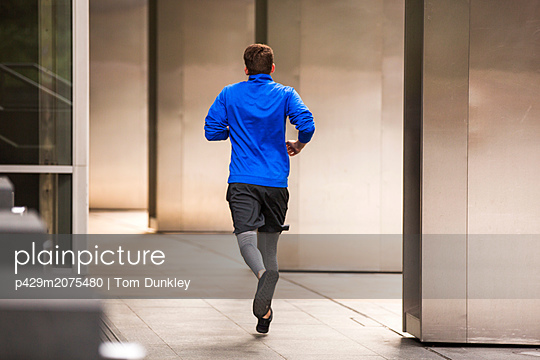 Young runner jogging on pavement, London, UK - p429m2075480 by Tom Dunkley