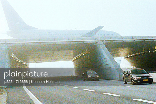 Commercial plane over viaduct and street traffic - p528m713858 by Kenneth Hellman