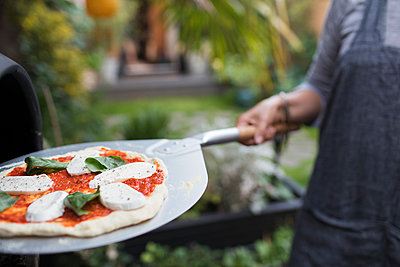 Woman cooking homemade pizza at pizza oven on patio - p1023m2208338 by Sam Edwards