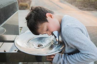 Thirsty boy drinking water from fountain at park - p1166m1545691 by Cavan Social