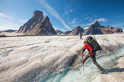 Mountaineer crosses a river on the Caribou Glacier, Baffin Island - p1166m2189720 by Cavan Images