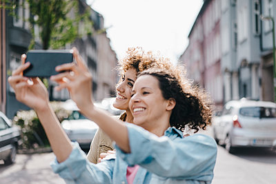 Best friends taking selfies with a smartphone in the city - p300m2012777 von Kniel Synnatzschke