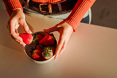 Woman holding fresh strawberries at dining table at home - p300m2266647 by DREAMSTOCK1982