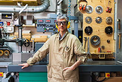 Mature male craftsperson with hand in pocket standing by machinery at workshop - p300m2294022 by Eugenio Marongiu