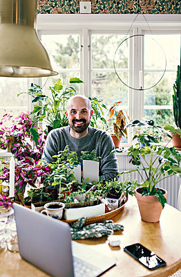 Portrait of smiling man sitting at table with plants against window in room - p426m2101783 by Maskot