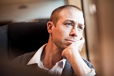 Thoughtful mature businessman sitting in train - p426m844676f by Maskot