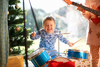 Boy and sister playing toy drum kit and guitar on christmas day - p429m1227230 by Peter Muller