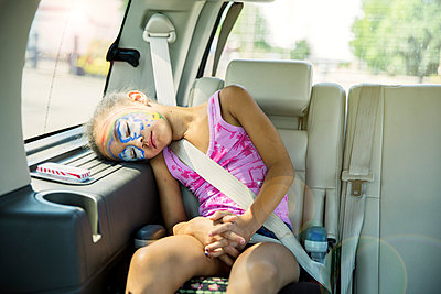 Mixed race girl in face paint sleeping in car back seat - p555m1413906 by Inti St Clair photography