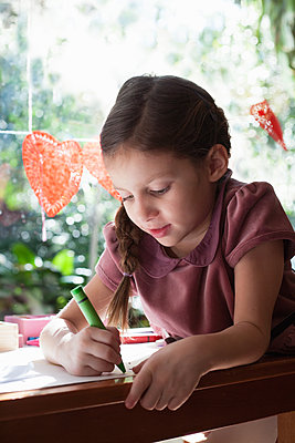 Girl sitting at window table drawing with crayon - p924m1404220 by Kinzie Riehm