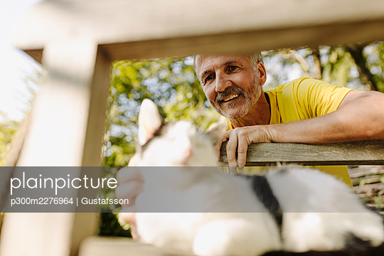Smiling mature man stroking cat on chair in back yard - p300m2276964 by Gustafsson