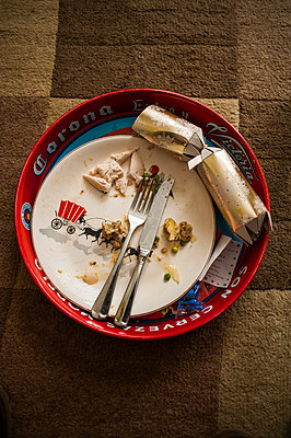 Finished Christmas dinner on a tray with a pulled cracker - p1047m1041624 by Sally Mundy