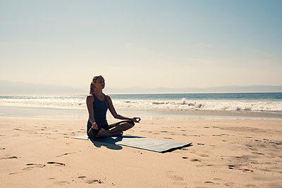 Young woman exercising yoga at a beach - p300m2078563 by André Babiak
