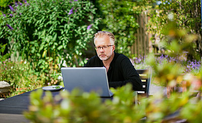 Denmark, Mon, Man working on laptop on patio - p352m1349033 by Pernille Tofte