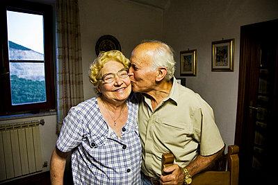 Senior man kissing senior woman in cheek - p528m713688 by Kari Kohvakka