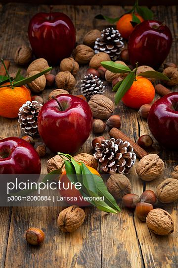 Red apples, tangerines, hazelnuts, walnuts, cinnamon sticks and pine cones on dark wood - p300m2080884 by Larissa Veronesi