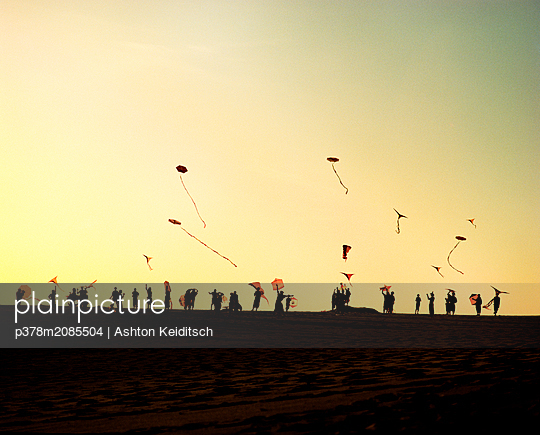 Silhouetted people and kites - p378m2085504 by Ashton Keiditsch
