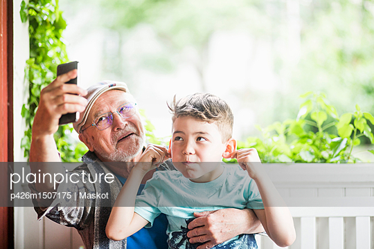 Grandfather taking selfie with grandson in porch - p426m1507175 by Maskot