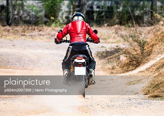 Man riding his scrambler type enduro motorbike on dirt track, rear view, Bangkok, Thailand - p924m2097359 by Henn Photography