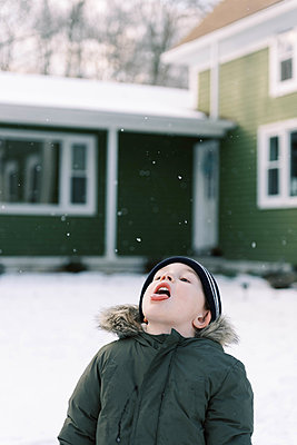 Little boy standing in his front yard trying to catch snow flakes. - p1166m2152176 by Cavan Images