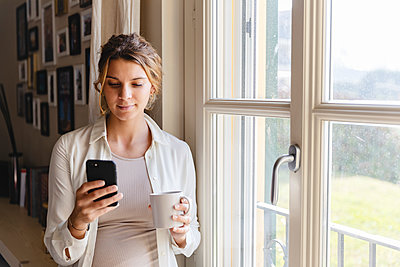 Young pregnant woman using smart phone by window at home - p300m2243191 by Michela Ravasio