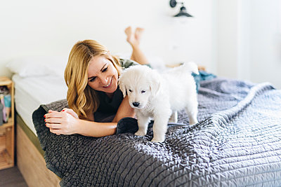 Smiling woman looking at Golden Retriever puppy while lying on bed - p300m2250493 by Daniel González