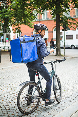 Food delivery man with bicycle using smart phone on street in city - p426m2145427 by Maskot