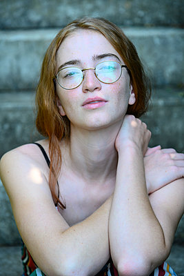 Teenage girl with eyeglasses on stone steps - p427m2209810 by Ralf Mohr