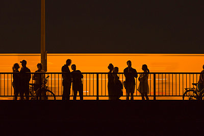 Group people waiting meeting bridge railings night evening silhouette - p609m2066585 by WALSH photography