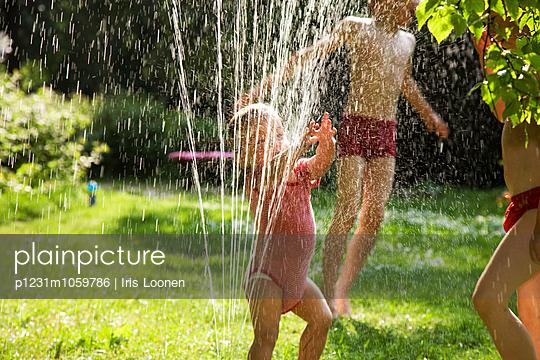 Children playing under the sprinkler - p1231m1059786 by Iris Loonen