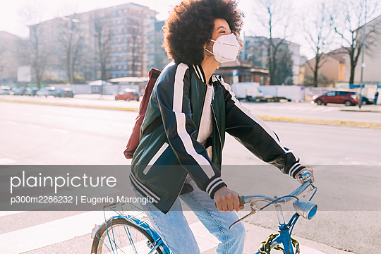 Woman with face mask cycling bicycle during sunny day - p300m2286232 by Eugenio Marongiu