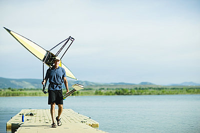 A middle-aged man carrying oars and a rowing shell on his shoulders, on a pontoon. - p1100m876300f by Jamie Kripke