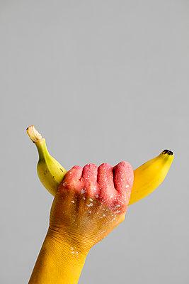 Rosa Hand - greift Banane - p1212m1128280 von harry + lidy