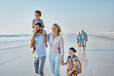Happy extended family strolling on the beach - p300m1450103 by Roger Richter