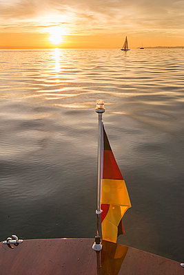 Germany, Baden-Wuerttemberg, Lake Constance, motorboat, German flag at sunset - p300m2082997 by Holger Spiering
