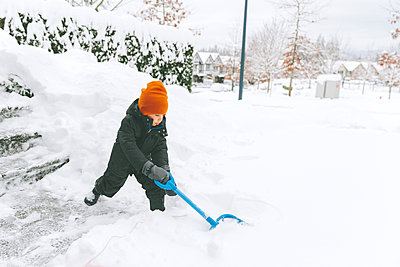 Little boy shoveling snow, Vancouver, Canada - p300m2166423 by Crystal Sing