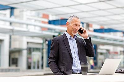 Businessman talking on smart phone at railroad station - p300m2287326 by Emma Innocenti