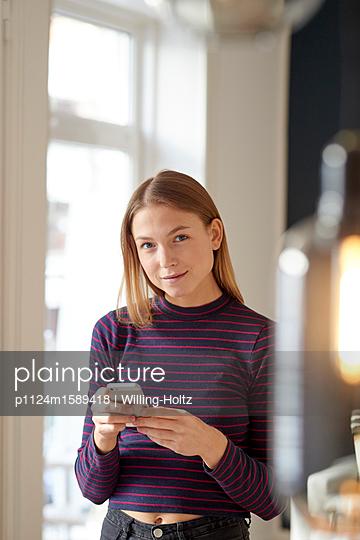 Junge Frau mit einem Smartphone - p1124m1589418 von Willing-Holtz