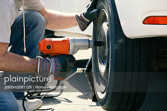 Man changing car tire, partial view - p300m2081126 by Roman Märzinger
