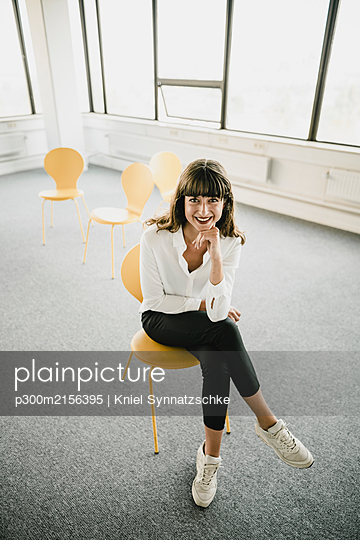 Smiling businesswoman sitting on a chair in an empty office - p300m2156395 by Kniel Synnatzschke