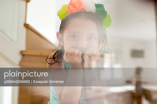Close-up of cute girl wearing colorful tiara looking through glass at home - p300m2206653 by Ezequiel Giménez