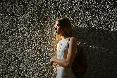 woman standing by textured wall - p1166m2137025 by Cavan Images